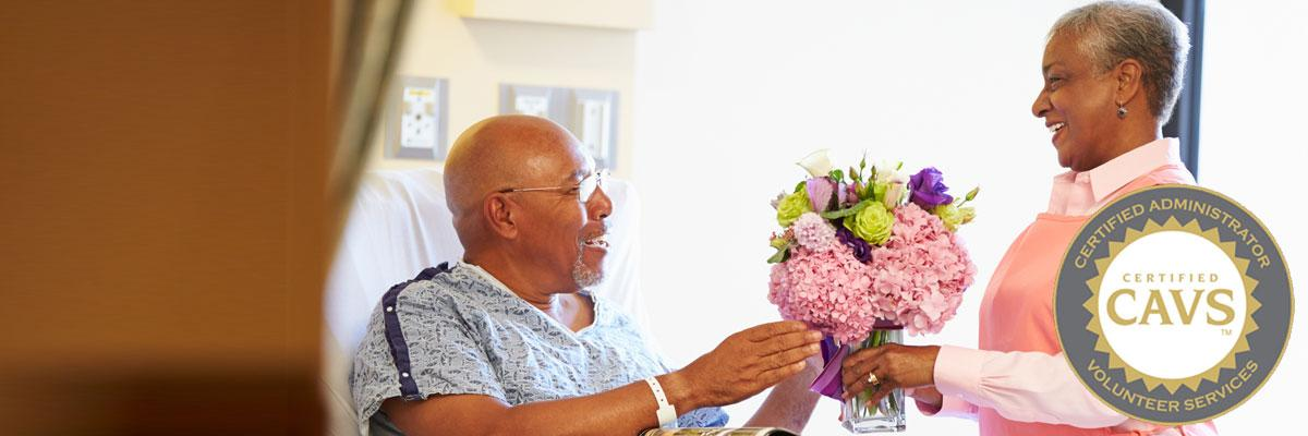 CAVS certification hospital volunteer giving patient flowers